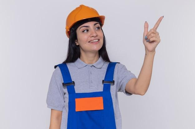Jeune femme constructeur en uniforme de construction et casque de sécurité à côté avec sourire sur visage heureux pointant avec l'index à quelque chose debout sur un mur blanc