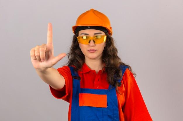 Jeune femme constructeur en uniforme de construction et casque de sécurité debout avec le doigt d'avertissement de danger sur mur blanc isolé