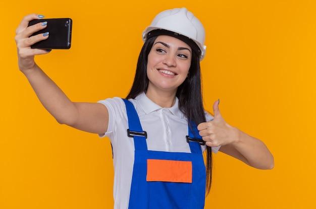 Jeune femme constructeur en uniforme de construction et casque de sécurité faisant selfie à l'aide de smartphone souriant confiant montrant le pouce debout sur le mur orange