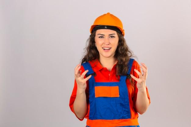 Jeune femme constructeur en uniforme de construction et casque de sécurité à la frustration de crier avec une expression agressive et les bras levés sur un mur blanc isolé