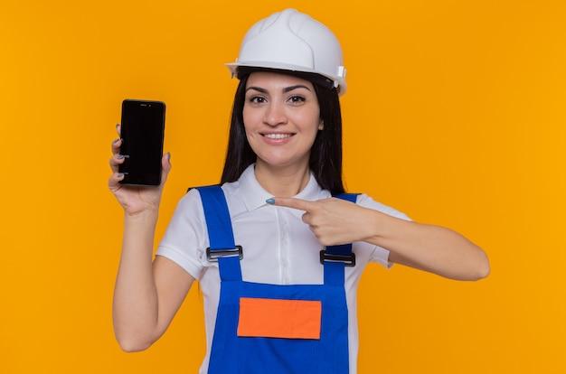 Jeune femme constructeur en uniforme de construction et casque de sécurité montrant smartphone pointant avec l'index sur elle souriant joyeusement debout sur le mur orange