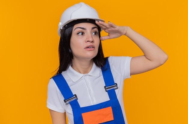 Jeune femme constructeur en uniforme de construction et casque de sécurité à la recherche de loin avec la main sur la tête pour regarder quelqu'un ou quelque chose debout sur un mur orange