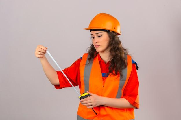 Jeune femme constructeur en uniforme de construction et casque de sécurité à la recherche de ruban de mesure avec visage sérieux sur mur blanc isolé