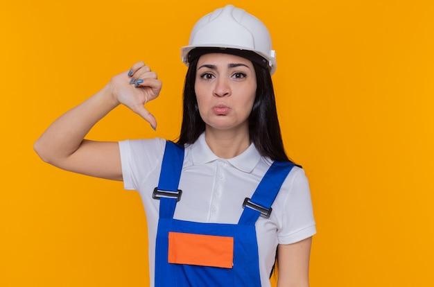 Jeune femme constructeur en uniforme de construction et casque de sécurité regardant la caméra