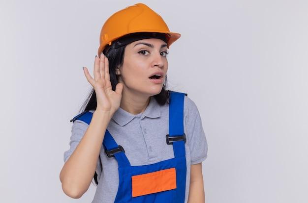Jeune femme constructeur en uniforme de construction et casque de sécurité tenant la main sur son oreille en essayant d'écouter les commérages debout sur un mur blanc