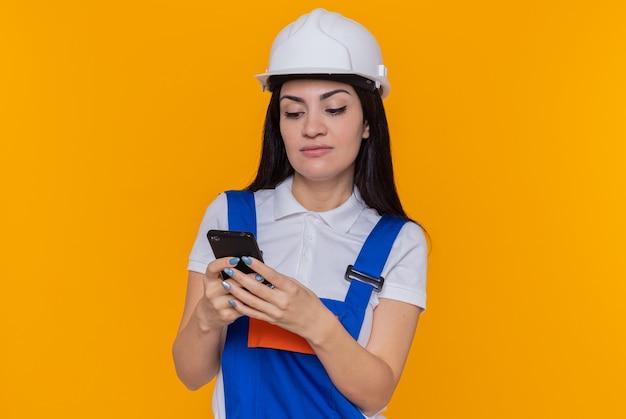 Jeune femme constructeur en uniforme de construction et casque de sécurité tenant smartphone en tapant divers messages avec visage sérieux debout sur un mur orange