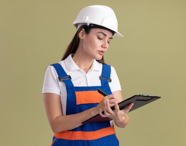 Jeune femme de construction confiante en uniforme écrivant quelque chose sur le presse-papiers isolé sur un mur vert olive
