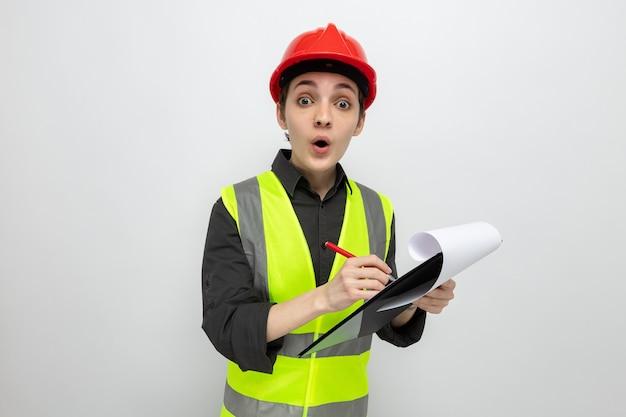 Jeune femme de construction en gilet de construction et casque de sécurité tenant un presse-papiers avec des pages blanches et un crayon surpris en prenant des notes debout sur blanc