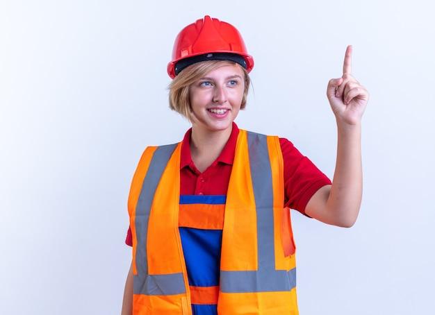 Jeune femme de construction impressionnée en uniforme pointe vers le haut isolé sur mur blanc