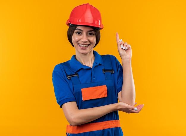 Une jeune femme de construction impressionnée en uniforme pointe vers le haut isolé sur un mur jaune