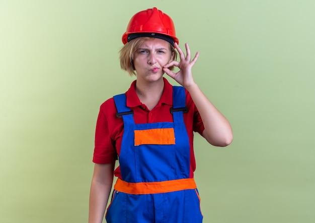 Jeune femme de construction suspecte en uniforme montrant un geste de silence isolé sur un mur vert olive