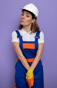 Jeune femme de construction timide en uniforme de construction et casque de sécurité dans des gants en caoutchouc avec les mains jointes debout sur un mur violet