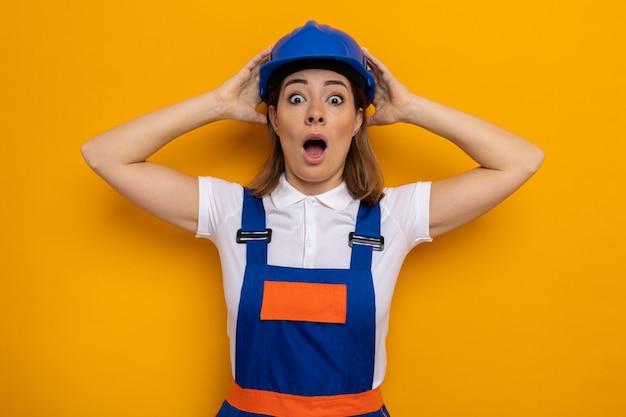 Jeune femme de construction en uniforme de construction et casque de sécurité étonnée et surprise avec les mains sur la tête debout sur le mur orange