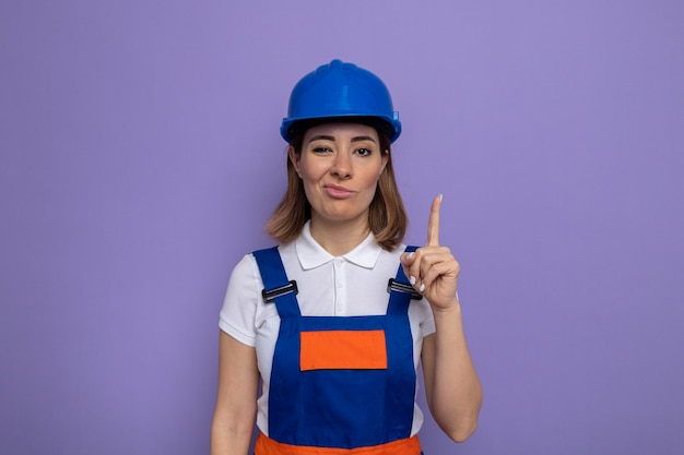 Jeune femme de construction en uniforme de construction et casque de sécurité faisant la bouche tordue avec une expression déçue montrant l'index debout sur le mur violet