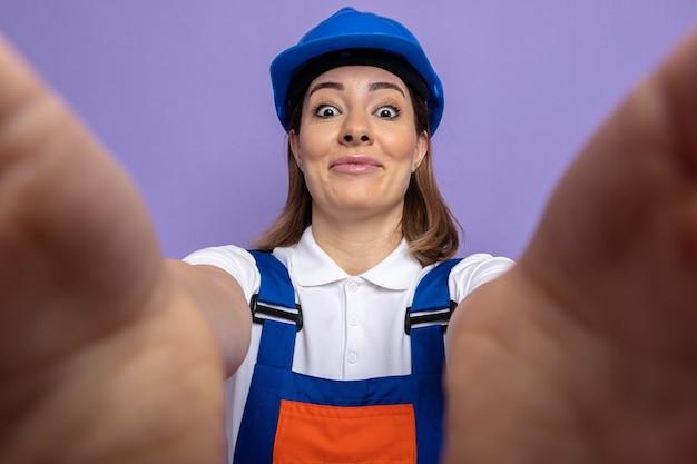 Jeune femme de construction en uniforme de construction et casque de sécurité heureux et positif souriant joyeusement debout sur le mur violet