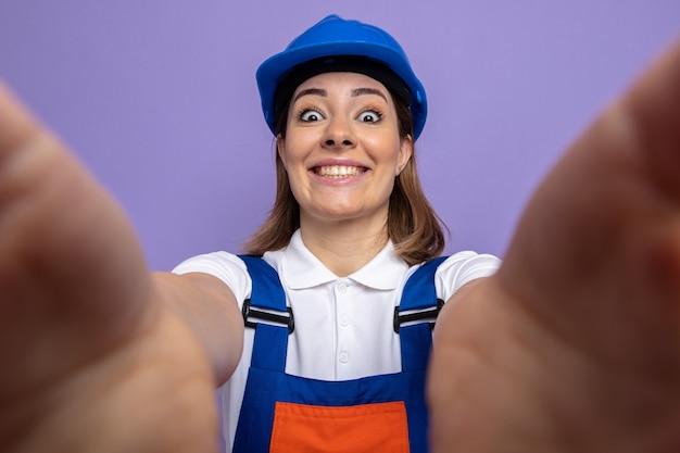 Jeune femme de construction en uniforme de construction et casque de sécurité heureux et positif souriant joyeusement debout sur violet