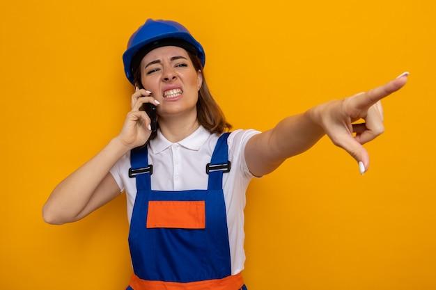 Jeune femme de construction en uniforme de construction et casque de sécurité regardant de côté, agacée et irritée, pointant avec l'index quelque chose tout en parlant au téléphone portable debout sur un mur orange