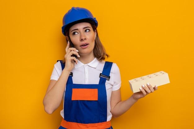 Jeune femme de construction en uniforme de construction et casque de sécurité semblant confuse tout en parlant sur un téléphone portable tenant une brique debout sur un mur orange