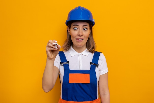 Jeune femme de construction en uniforme de construction et casque de sécurité avec un sourire narquois sur le visage écrivant avec un stylo dans l'air debout sur un mur orange