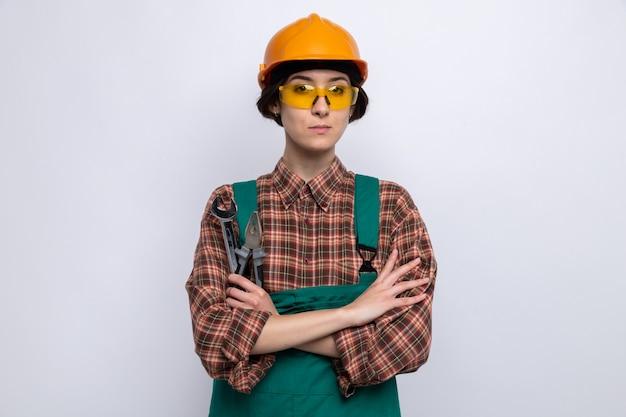 Jeune femme de construction en uniforme de construction et casque de sécurité tenant une clé avec une pince avec une expression sérieuse et confiante, les bras croisés, debout sur un mur blanc