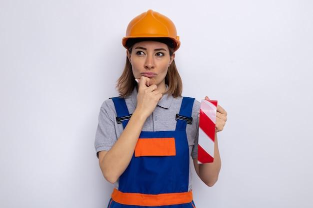 Jeune femme de construction en uniforme de construction et casque de sécurité tenant du ruban adhésif regardant de côté avec une expression pensive avec la main sur son menton debout sur un mur blanc