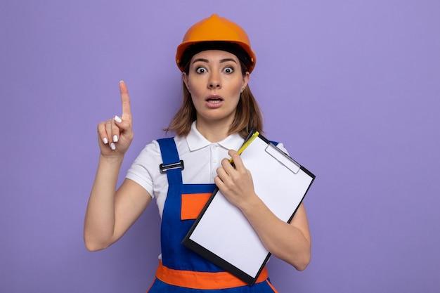Jeune femme de construction en uniforme de construction et casque de sécurité tenant un presse-papiers avec des pages blanches l'air surpris montrant l'index ayant une nouvelle idée debout sur un mur violet