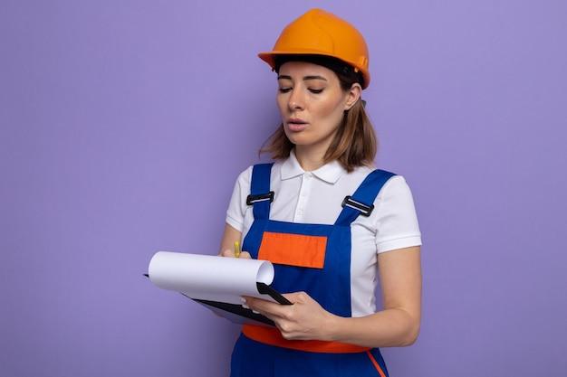 Jeune femme de construction en uniforme de construction et casque de sécurité tenant un presse-papiers avec des pages blanches le regardant avec un visage sérieux prenant des notes sur un mur violet
