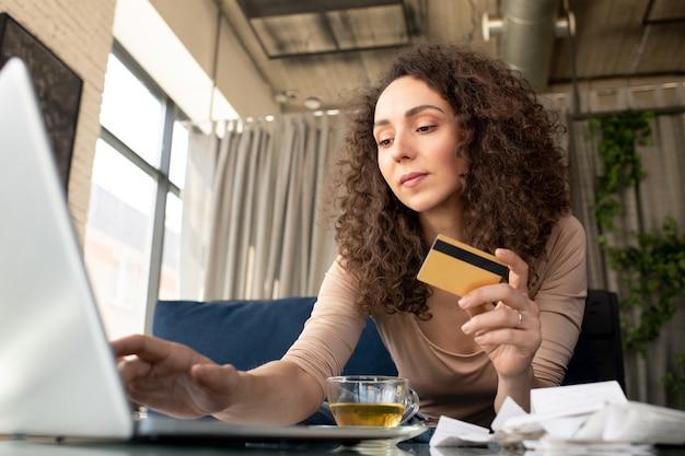 Jeune femme contemporaine en tenue décontractée ayant une tisane et regardant l'écran de l'ordinateur portable