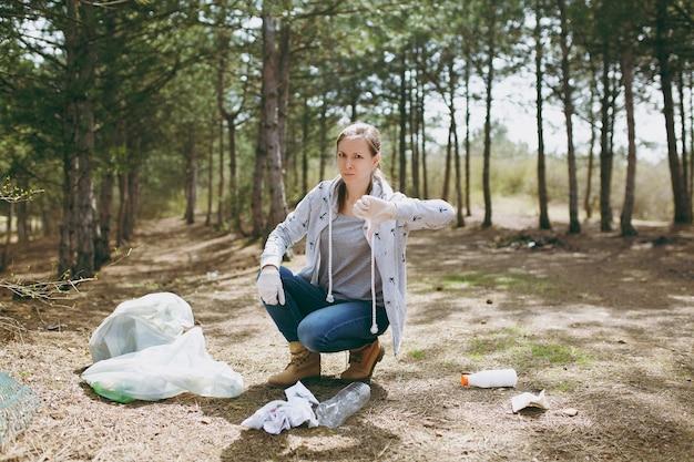 Jeune femme contrariée dans des vêtements décontractés et des gants nettoyant les ordures et montrant le pouce vers le bas près des sacs poubelles dans le parc. problème de pollution de l'environnement