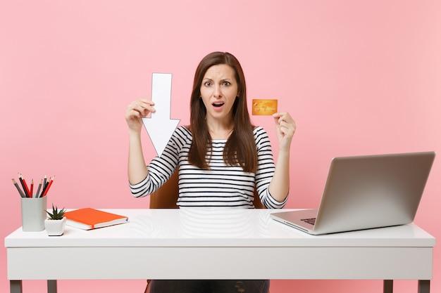 Jeune femme contrariée tenant la flèche d'automne de la valeur, la carte de crédit s'assoit et travaille au bureau blanc avec un ordinateur portable contemporain isolé sur fond rose pastel. concept de carrière d'entreprise de réalisation. espace de copie.