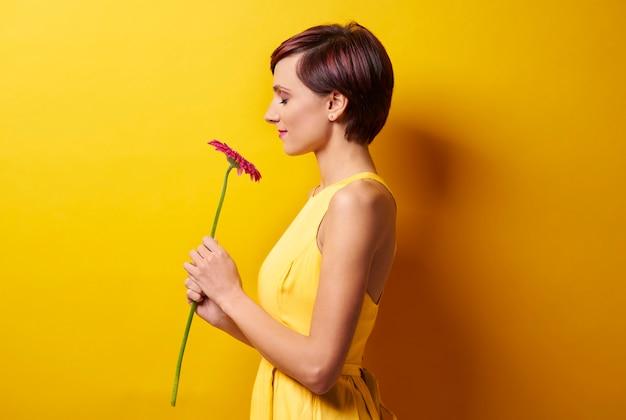 Jeune femme contre le mur jaune