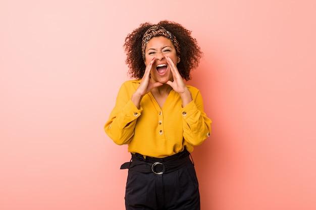 Jeune femme contre un mur rose criant excité à l'avant