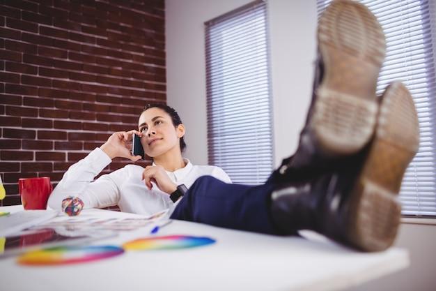 Jeune, femme, conversation, téléphone, bureau