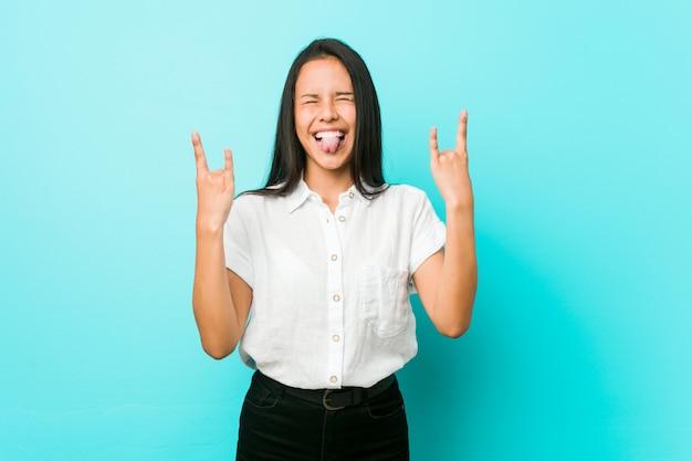 Jeune femme cool hispanique contre un mur bleu montrant le geste de la roche avec les doigts