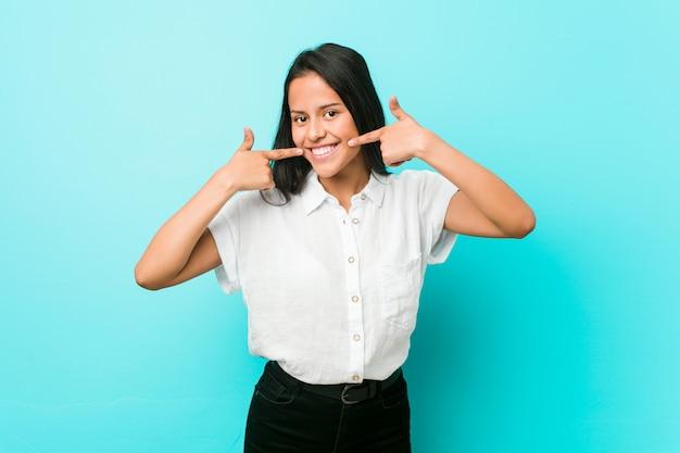 Jeune femme cool hispanique contre un mur bleu sourit, pointant les doigts sur la bouche.