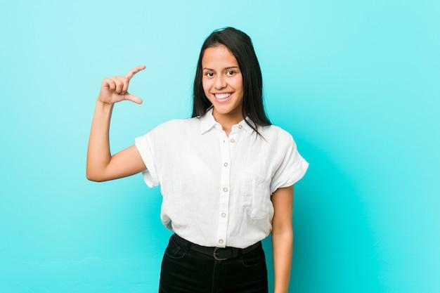 Jeune femme cool hispanique contre un mur bleu tenant quelque chose de peu avec les index, souriant et confiant.