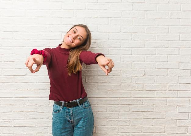 Jeune femme cool sur un mur de briques gai et souriant pointant vers l'avant