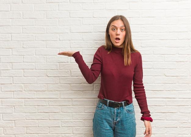 Jeune femme cool sur un mur de briques tenant quelque chose sur la main de la paume