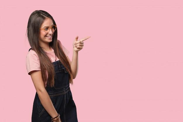 Jeune femme cool pointant vers le côté avec le doigt