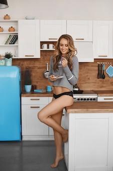 Jeune femme avec un corps parfait en culotte et sweat-shirt prenant son petit déjeuner dans la cuisine