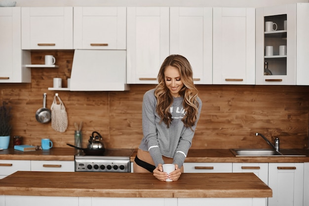 Jeune femme avec un corps parfait en culotte et sweat-shirt en train de prendre un café dans la cuisine
