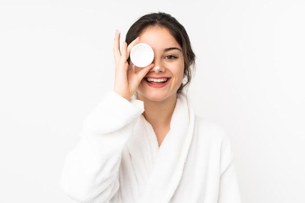 Jeune femme avec des cosmétiques sur un mur isolé