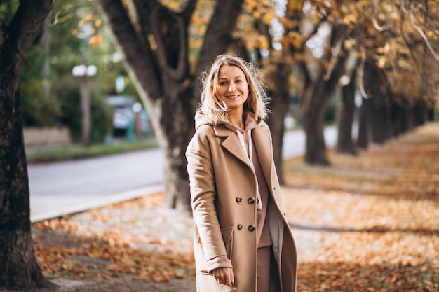 Jeune femme en costume beige à l'extérieur dans un parc en automne