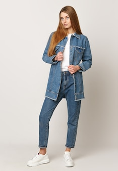 Jeune femme en costume en jean sur fond blanc. concept de photo publicitaire pour les vêtements.