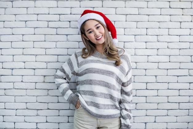 Jeune femme en costume de noël sur fond de briques blanches.