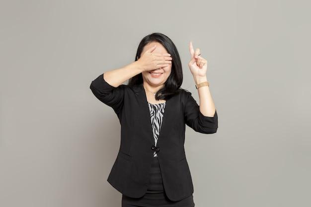 Jeune femme en costume noir pointe vers le haut tout en se couvrant les yeux avec ses mains
