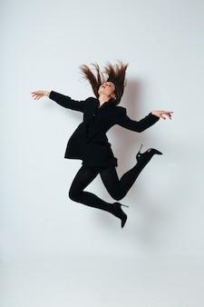 Jeune femme en costume noir sautant sur fond blanc. fille en noir isolé