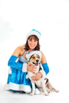 Jeune femme en costume de père noël est assise avec un chien dans un chapeau sur fond blanc