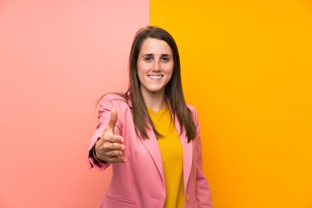 Jeune femme avec costume rose sur poignée de main fond coloré après bonne affaire