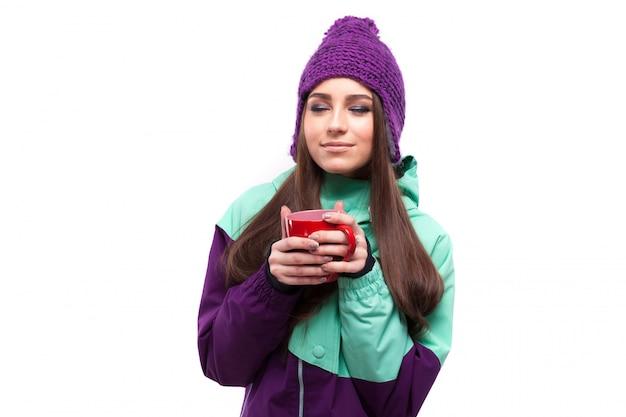 Jeune femme en costume de ski pourpre tenir une tasse rouge